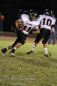 Sylvan-Lucas Mustang Coby Hower (#11) carries the ball during the Sylvan-Lucas vs Otis-Bison High School football game with Otis-Bison winning 32 to 30 at Otis-Bison High School Field in Otis, Kansas on October 31, 2013.  (Photo: Joey Bahr, www.joeybahr.com)