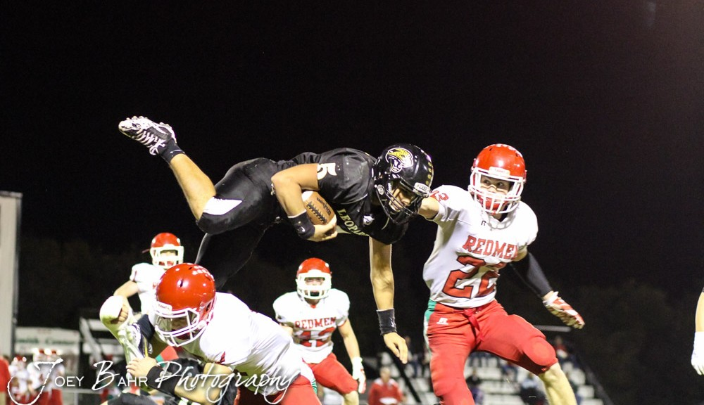 LaCrosse Leopard Jack Garcia (#5) tries to hurdle Smith Center Redman Lt Meitler (#1) during the Smith Center Redmen at LaCrosse Leopards High School Football Game with LaCrosse winning 48 to 14 at Bill Schoendaller Athletic Field in LaCrosse, Kansas on October 17, 2014.  (Photo: Joey Bahr, www.joeybahr.com)