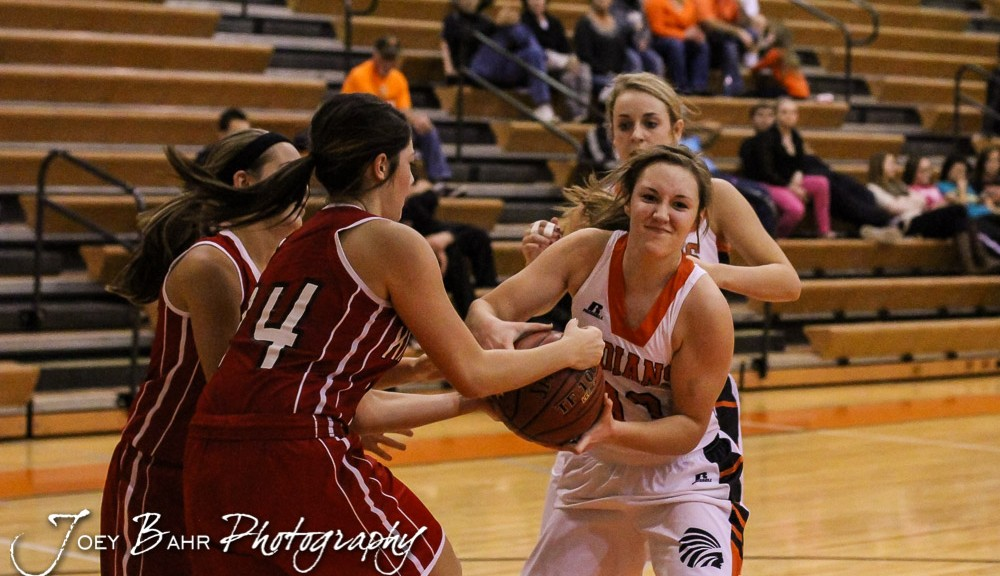 Kinsley Lady Coyote Shelby Hattrup (#14) and Larned Lady Indian Haley Skelton (#13) fight for a loose ball during Seventh Annual Keady Basketball Classic First Round game between the Kinsley Lady Coyotes and the Larned Lady Indians with Kinsley winning 47 to 31 at Larned Middle School in Larned, Kansas on December 8, 2014.  (Photo: Joey Bahr, www.joeybahr.com)
