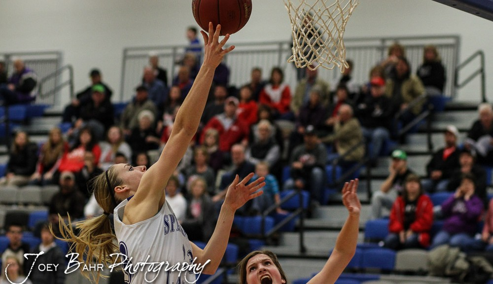 Spearville Lady Lancer Cody Offerle (#23) goes for a layup as Kinsley Lady Coyote Scout Frame (#15) defends during the 2A Sub-State First Round Game with the Spearville Lady Lancers vs the Kinsley Lady Coyotes with Spearville winning 66 to 53 at Spearville High School in Spearville, Kansas on March 3, 2015.  (Photo: Joey Bahr, www.joeybahr.com)