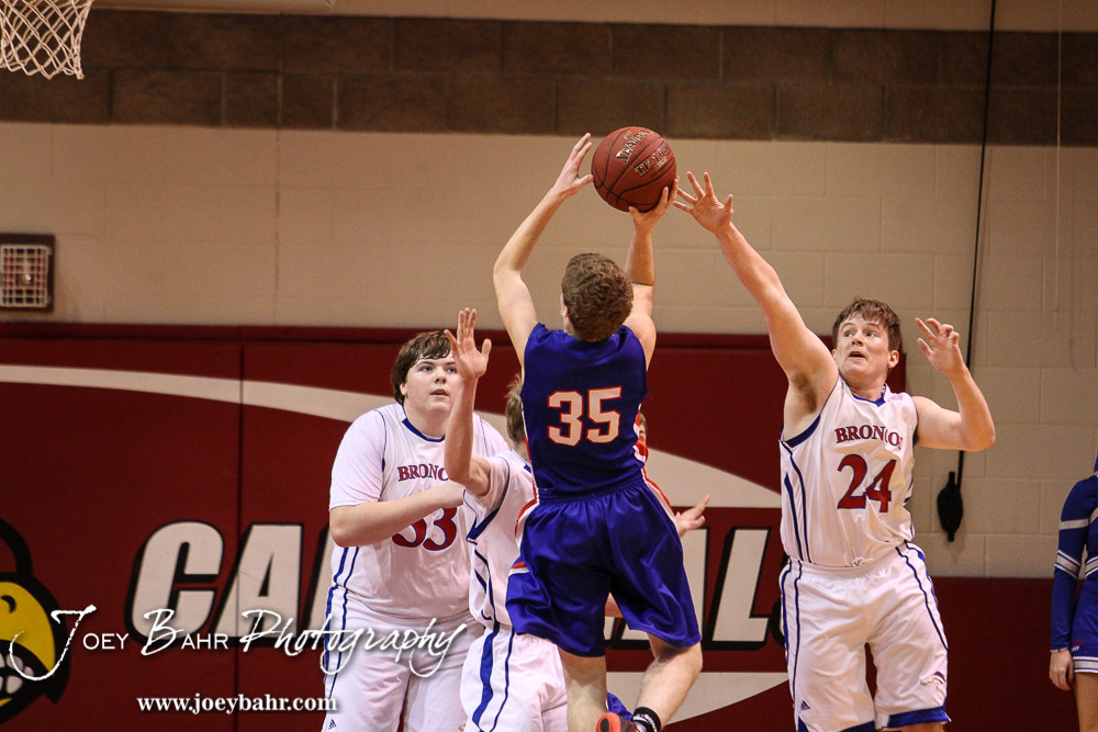 Russell Bronco Zach Boxberger (#24) tires to block a shot by Ellinwood Eagle Nathan Monday (#35) during the 2016 Hoisington Winter Jam Boys Thrid Place Basketball game between the Ellinwood Eagles and the Russell Broncos with Ellinwood winning 47 to 37 of Hoisington Activity Center in Hoisington, Kansas on January 23, 2016. (Photo: Joey Bahr, www.joeybahr.com)
