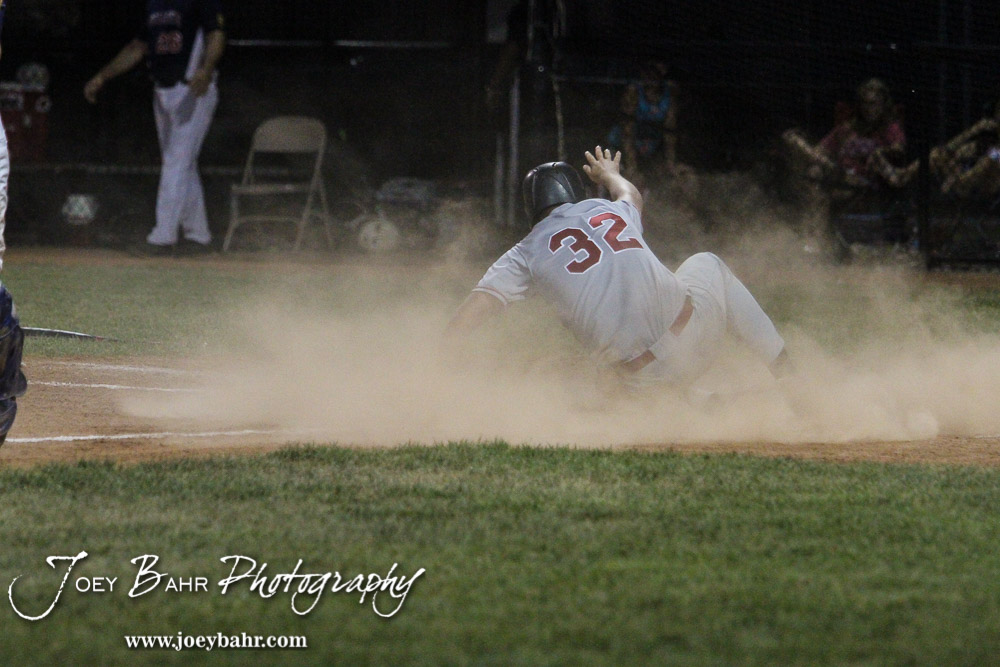 Great Bend Braves #32 Blaine Mermis slides into home plate. The Buhler Nationals defeated the Great Bend Braves 7 to 3 in the American Legional Class A Baseball State Tournament Semifinal at the Great Bend Sports Complex in Great Bend, Kansas on July 21, 2016. (Photo: Joey Bahr, www.joeybahr.com)