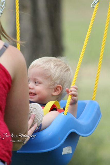 Charlie smiles as Mommy pulls back on the swing